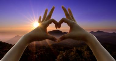 ハートの形にした手、空、太陽の光